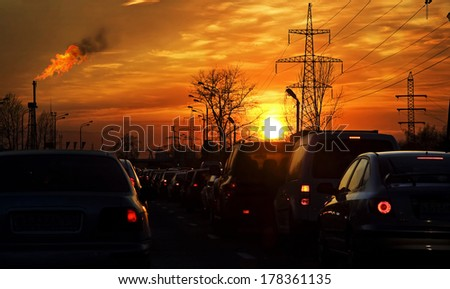 Car traffic against the sunset background and refinery. - stock photo