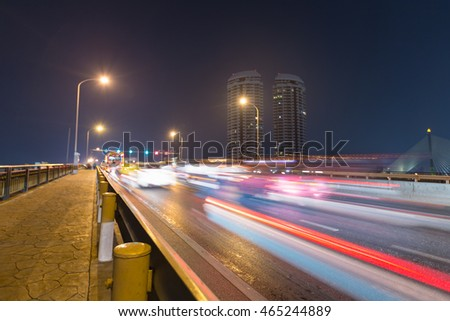 Car traffic on the bridge. At night time. The bridge lights street