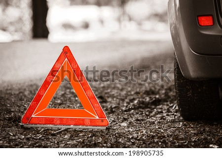 Car transportation. Breakdown of car transporation. Closeup of red warning triangle sign symbol on the forest road. - stock photo