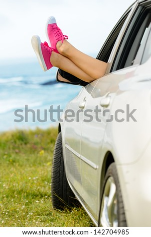 Car travel vacation and relax concept. Woman legs out the windows enjoying freedom and relaxing on nature coast landscape. - stock photo