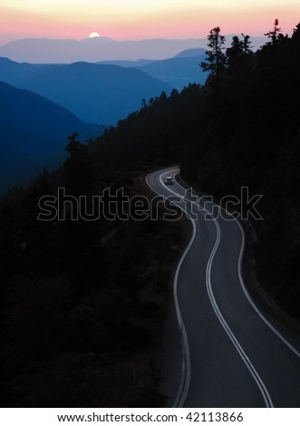 car traveling winding road between mountain at sunset - stock photo