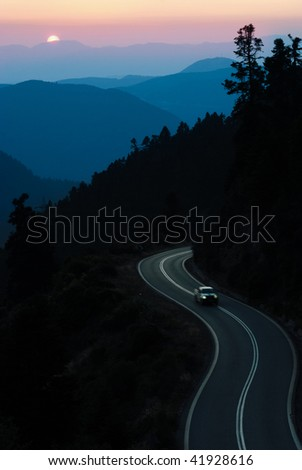 car travelling winding road between mountain at sunset - stock photo