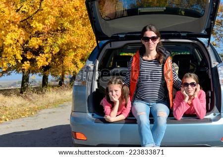 Car trip on autumn family vacation, happy mother and kids travel and have fun, car insurance concept  - stock photo