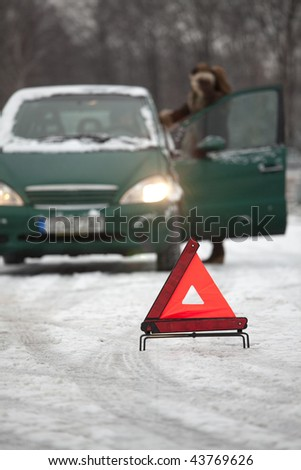 car trouble on the road - warning triangle on foreground - stock photo