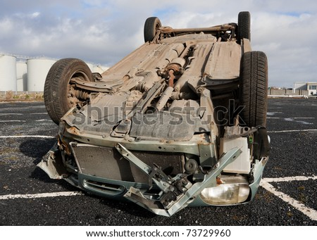 car turned upside-down after road collision - stock photo