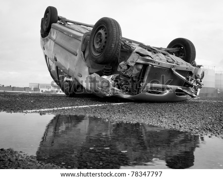 car turned upside-down after road collision and reflection in the water - stock photo