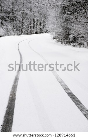 Car tyre traces on a mountain curved road - stock photo