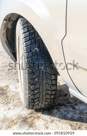 Car tyre with winter treads resting on dirty grey snow - stock photo