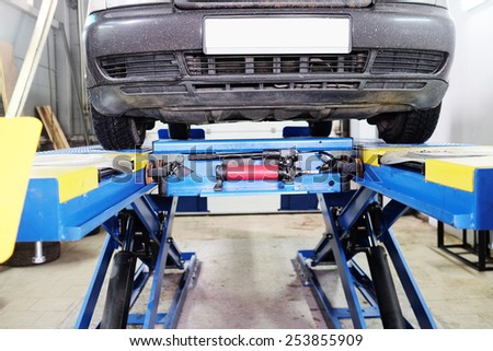Car under repair on hoist at service station - stock photo