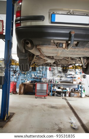Car under repair on service lift in garage - stock photo