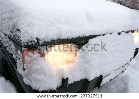 Car under snow with the  headlights on, outdoor close up shot - stock photo