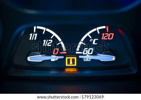 Car, vehicle interior with visible Fuel, gas gauge and Engine coolant temperature gauge with illuminated Information warning lamp visible. - stock photo