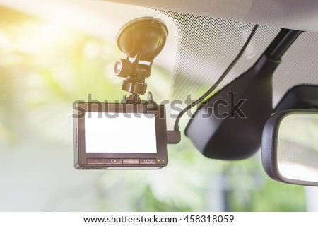 car video recorder installed on the window,with blank screen,copyspace ,selective focus.at sunset,vintage color