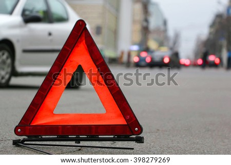 Car warning triangle on the road. - stock photo