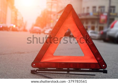 Car warning triangle on the road against the city in the evening. Red warning triangle with a car.