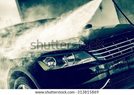 Car Wash Closeup. Washing Modern Car by High Pressure Water. - stock photo