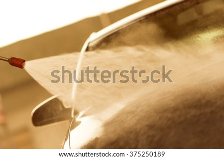 Car wash with high pressure washer - stock photo