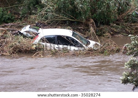 Car washed away by raging floodwaters - stock photo