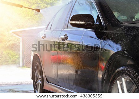 Car washing with flowing water. Outdoor Self Service Cleaning Car Using High Pressure Water