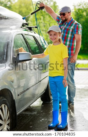 Car-washing - Young girl with father in carwash. - stock photo