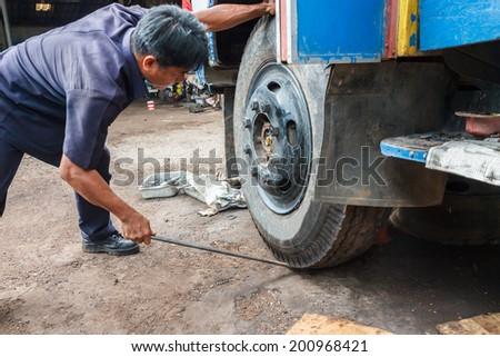 Car wheel changed by mechanic - stock photo