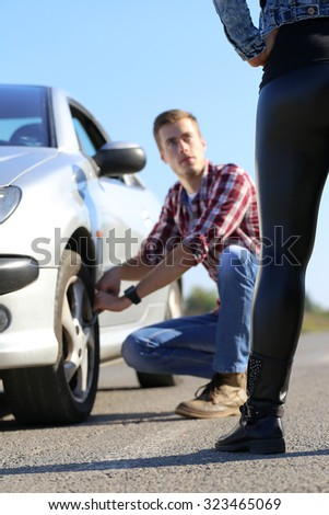 Car wheel defect man change puncture tire , while woman waiting - stock photo