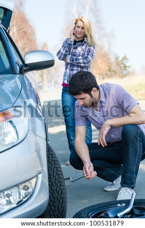 Car wheel defect man change puncture tire woman calling assistance