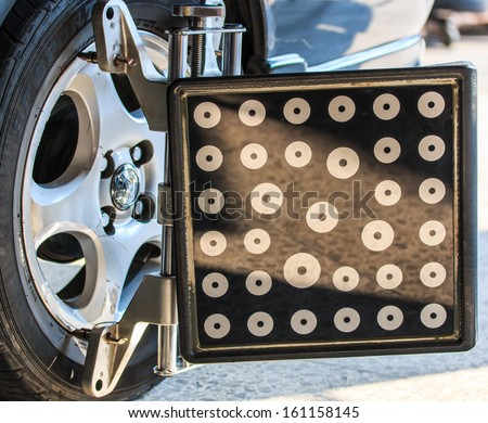 Car wheel fixed with computerized wheel alignment machine clamp - stock photo