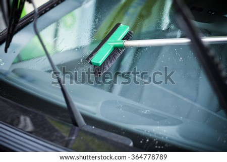 Car window squeegee cleaning the windscreen with two black windshield wipers - stock photo