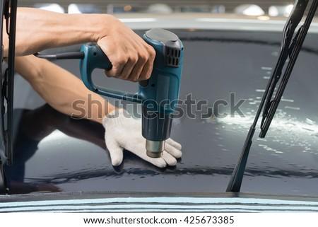 Car window tinting series : Heat shrinking car window film - stock photo