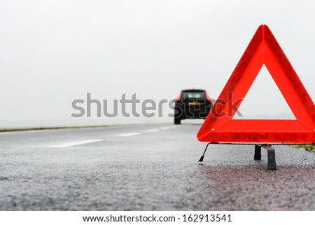 car with a breakdown on a rainy autumn day in the middle of nowhere - stock photo
