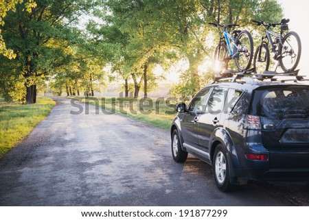 Car with bicycles in the forest road at sunset - stock photo
