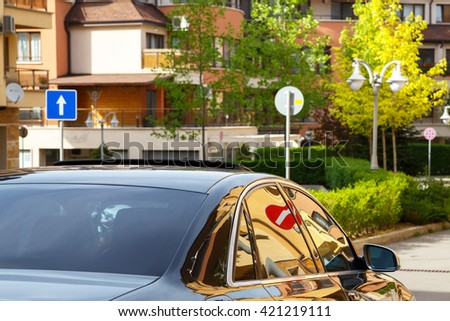 Car with dark tinted windows driving down a residential urban street with apartment blocks and multi-storey houses with a no entry sign reflected in the glass - stock photo