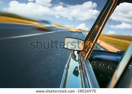 Car with mirror and dashboard on blurred asphalt road with another cars - stock photo
