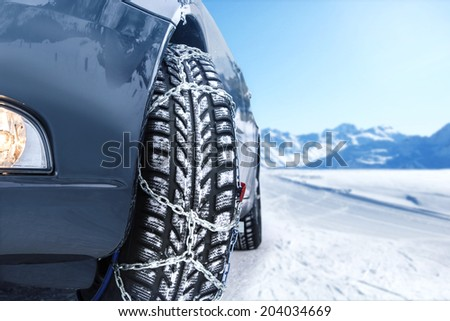 Car with mounted snow chains in wintry environment - stock photo