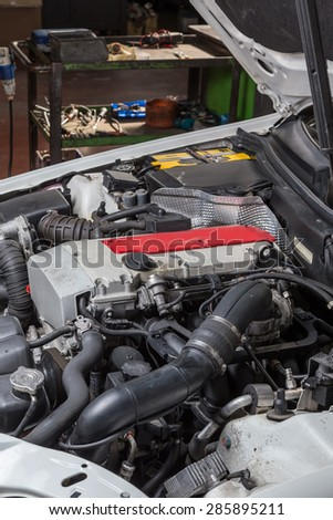 car with the hood open in repair workshop - stock photo