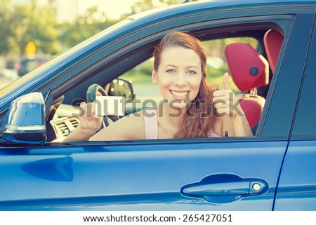 Car. Woman driver happy smiling showing thumbs up coming out of car window on summer day  - stock photo