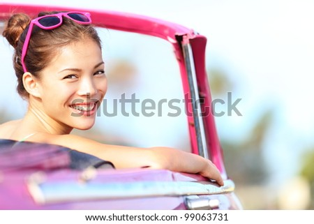Car woman happy in old pink retro vintage car. Young woman driving on road trip on beautiful sunny summer day. Pretty mixed race Asian / Caucasian female model.