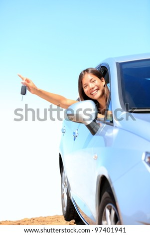 Car woman showing keys excited, happy and joyful. Young woman driver smiling in her new car. Mixed race Asian / Caucasian female model above the clouds on beautiful summer day. - stock photo