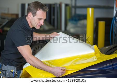Car wrapper preparing yellow foil to wrap a vehicle - stock photo