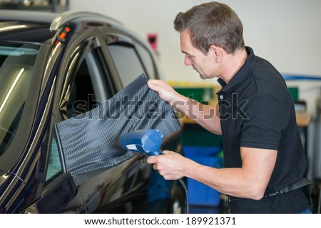 car wrapper wrapping side mirror with vinyl film or foil using a heat gun - stock photo