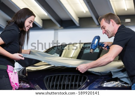 Car wrappers attach a grey vinyl foil to vehicle - stock photo
