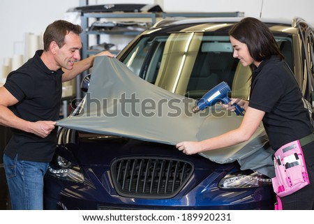 Car wrappers attach a grey vinyl foil to vehicle