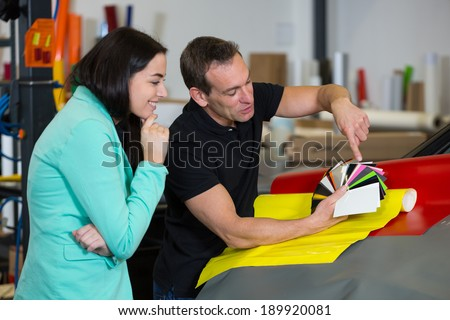 Car wrapping professional consulting a client about vinyl films or foils - stock photo