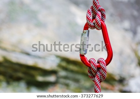 carabiner with rope on rocky background - stock photo