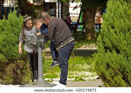 CARACAL, ROMANIA   MAY 01, 2016: Family In Park Drinking Water Outside From