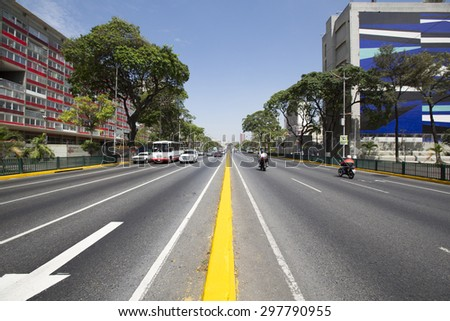 CARACAS, VENEZUELA, APRIL 20: Avenue with small traffic, bus, cars and motos, early in the morning in Caracas against a blue sky, Venezuela 2015. - stock photo