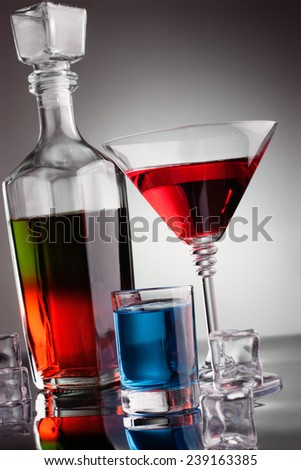 Carafe and glasses of multicoloured alcohol drinks with ice - stock photo