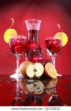 Carafe and sangria or fruit punch glasses wedged with an orange slice and maraschino cherry - stock photo