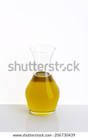 carafe of fresh olive oil on white table